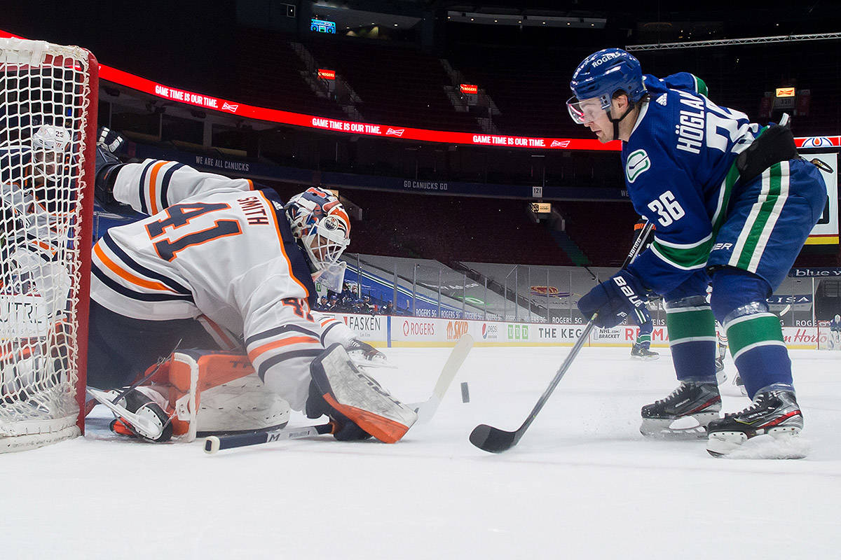 Edmonton Oilers goalie Mike Smith (41) stops Vancouver Canucks' Nils Hoglander (36), of Sweden, during the first period of an NHL hockey game in Vancouver, on Tuesday, May 4, 2021. THE CANADIAN PRESS/Darryl Dyck